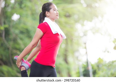 A portrait of a asian woman doing stretching exercise during outdoor cross training workout