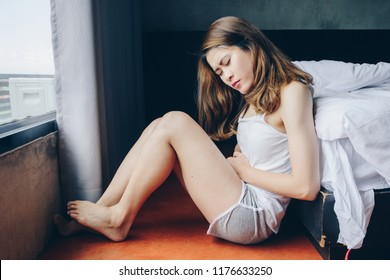 Portrait of Asian woman having painful stomachache in bedroom. Conceptual of woman suffering stomach ache, menstrual pain, period cramp or abdominal pain during pregnancy.