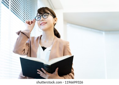 Portrait of asian woman holding a book.