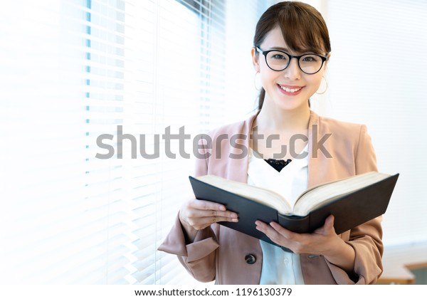 Portrait of a asian woman holding a book.