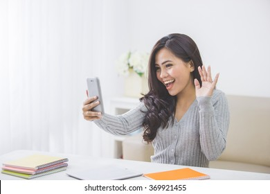 portrait of asian woman at home making a video call using smart phone