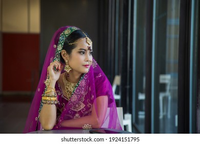 Portrait Asian woman in a magenta Indian tradition sari, she is looking at side next to the long glass window at office