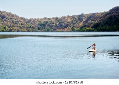 Portrait of asian woman paddling a kayak on the lake in satonda island. Sumbawa, Indonesia