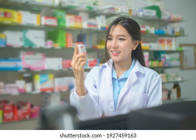 A portrait of asian woman pharmacist wearing lab coat in a modern pharmacy drugstore.