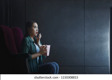 Portrait of asian woman with popcorn watching horror movie at home