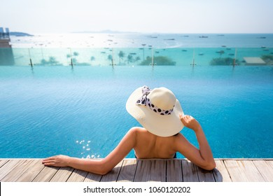Portrait of asian woman relaxing in swimming pool with sunbathe.