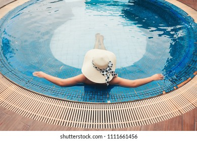 Portrait of asian woman relaxing in swimming pool and sunbathing.