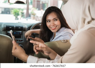 portrait of asian woman showing direction to the driver using GPS in her mobile phone