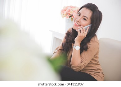 portrait of  asian Woman sitting on a couch, calling friend with smartphone