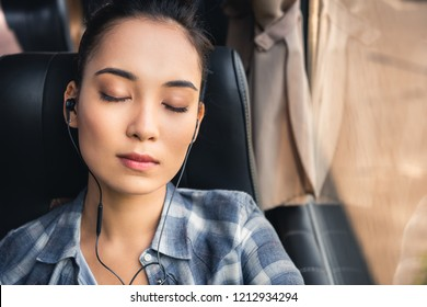portrait of asian woman sleeping and listening music in earphones during trip on travel bus