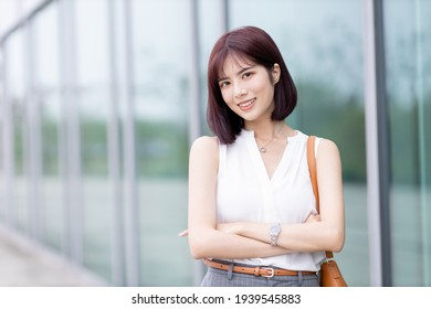 Portrait of Asian Woman Smiling Charmingly while Standing in the Middle of Modern Urban City - looking at camera and smiling