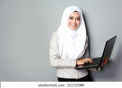 portrait of asian woman smiling while using laptop computer