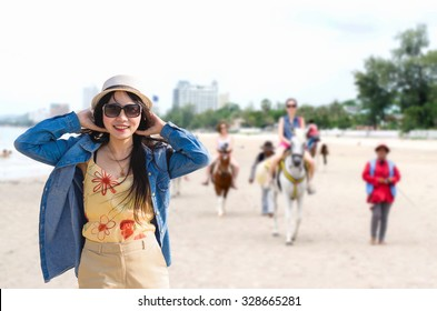 A portrait of Asian woman solo travel on the beach - young attractive female touching hat and traveling at Hua Hin beach, Thailand in summer concept