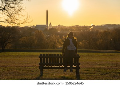 Portrait of asian woman tourist sitting over the Washington DC Landmark which can see United states Capitol, washington monument and lincoln memorial at the sunrise time, history and culture concept