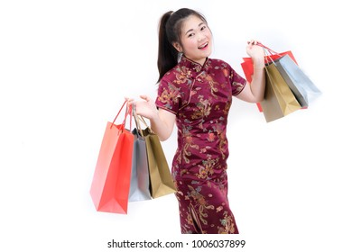 Portrait of asian woman in traditional chinese long dress, cheongsam, black hair, carrying paper shopping bags as a customer for Chinese New Year festival, celebration time, happy feeling, joyful