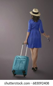 Portrait of asian woman traveling with suitcase over dark background
