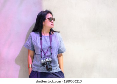 portrait of asian woman wear sunglasses with camera leaning at concrete wall with sunshade in day light.fashion traveler.