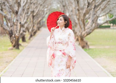 portrait of asian woman wearing kimono holding traditional red umbrella