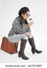 Portrait of Asian woman wearing winter jacket and sitting on vintage brown bag, and drinking coffee cup.