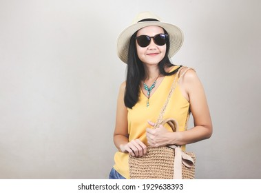 Portrait of asian woman  wearing yellow sleeveless shirt, hat and sunglasses  holding woven bag, standing on white background, smiling and looking at camera. Summer concept.