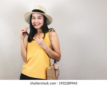 Portrait of Asian woman  wearing yellow sleeveless shirt and hat, holding woven bag, standing on white background, holding  sunglasses , smiling and looking at camera. Summer concept.
