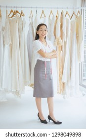 Portrait of asian woman wedding dress store owner standing and cross arm,Beautiful dressmaker in shop and small business,Happy and smiling positive thinking