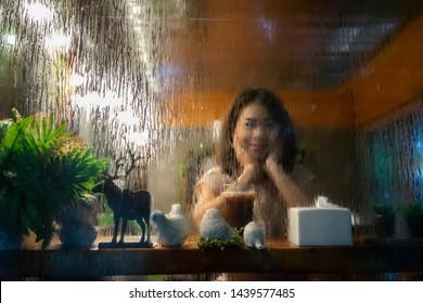 Portrait Asian women Sit alone in coffee shop Past mirror raining