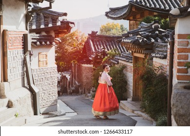 Portrait Asian women wearing hanbok at the traditional style houses of Bukchon Hanok Village in Seoul, South Korea, Vintage color.