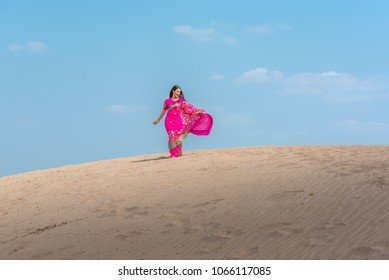 c77a639a15 Portrait of Asian young beautiful woman wearing traditional indian dress on  desert and blue sky background