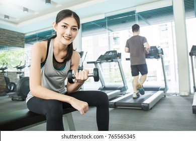 Portrait of Asian young beautiful woman holding dumbbell training hard, asian woman workout  at the gym sport club, healthcare and medical concept