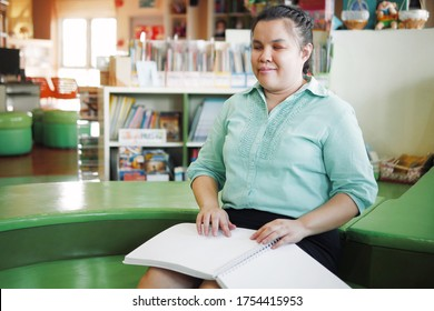 Portrait of Asian young blind person woman disabled people reading Braille book in creative workplace
