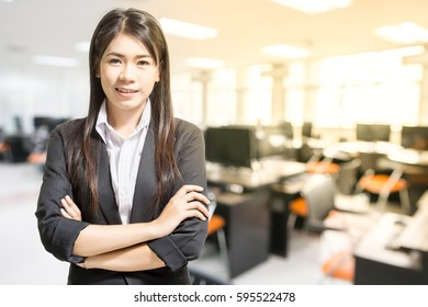 Portrait of Asian young business woman smiling in the office with copy space.