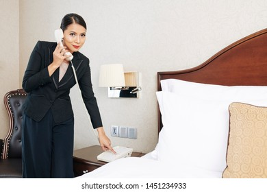 Portrait of Asian young businesswoman in black suit looking at camera while check in to the hotel room and call on reception