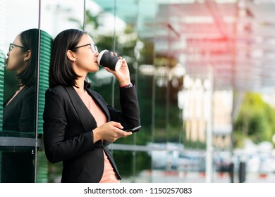 Portrait Asian young businesswoman drinking morning coffee and hand holding phone on urban