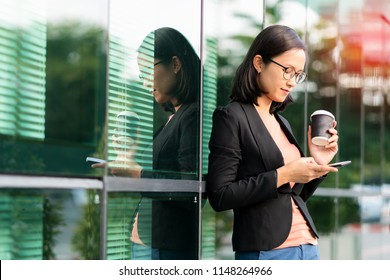 Portrait Asian young businesswoman hand holding morning coffee and reading phone on urban