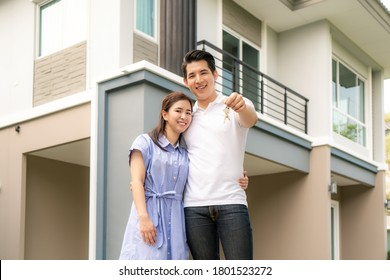 Portrait of Asian young couple standing and hugging together and holding house key looking happy in front of their new house to start new life. Family, age, home, real estate and people concept.