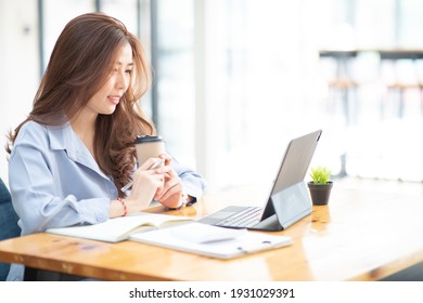 Portrait of Asian Young Female working financial report with tablet at home office.