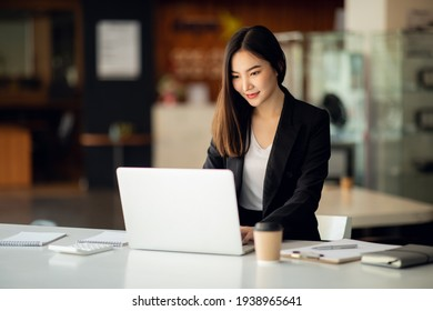 Portrait of Asian young female working on laptop at office