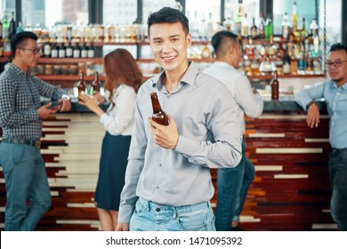 Portrait of Asian young man holding bottle of beer and smiling at camera with other people standing near the bar counter in the background in the bar