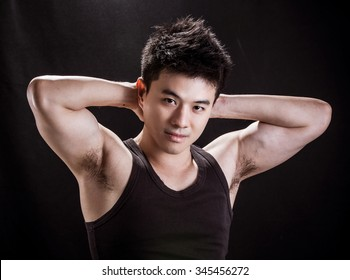 Portrait of Asian young man on black background - Show muscle and strengh