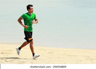 A portrait of a Asian young man running on beach, Sport concept