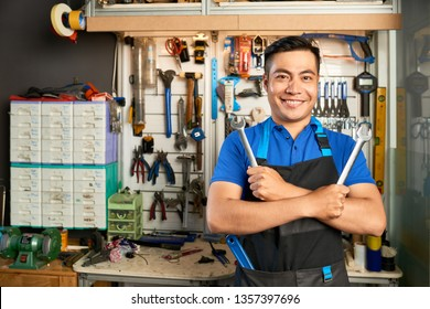 Portrait of Asian young mechanic in apron holding two spanners and smiling at camera in workshop