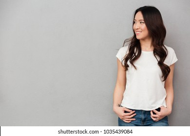 Portrait of asian young woman with dark curly hair posing on camera and looking aside on copyspace isolated over gray background