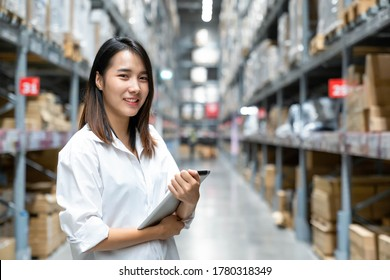 Portrait of Asian young woman enjoying and smile doing checking stock of products in warehouse by using a tablet checking inventory levels , Logistics concept.