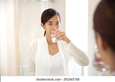 A portrait of an Asian young woman gargle on her mouth after tooth brushing