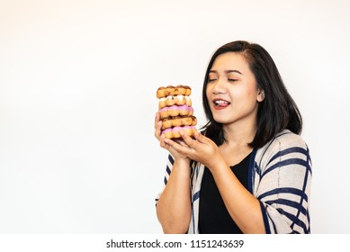 Portrait Asian young woman holding and eating donut on white background.Unhealthy dessert food concept.