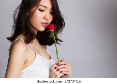 Portrait of asian young woman with red rose flower