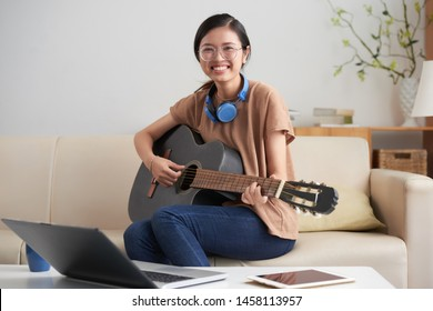 Portrait of Asian young woman sitting on sofa in front of table with laptop and smiling at camera while playing on guitar at home