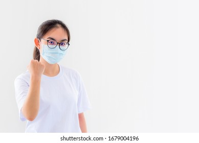 Portrait Asian young woman wears glasses and mask to protect against Coronavirus, girl show a fist encourage to fight contagious disease concept stop virus Covid 19 outbreak to win on white background