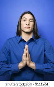 Portrait of Asian-American teen boy with hands pressed together in prayer position standing against blue background.